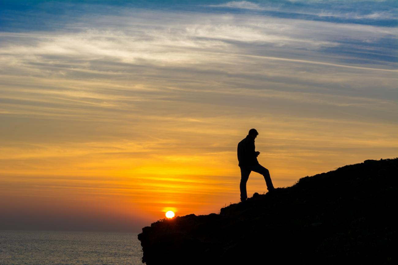 man standing on cliff with sunset in background